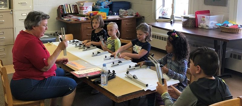 Children sitting at a table learning how to play musical bells